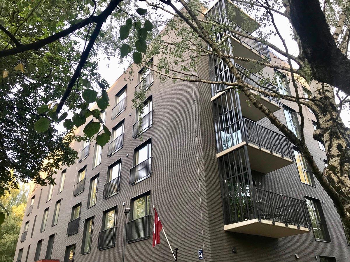 Dzīvojamā māja Āgenskalna priedēs ar metāla franču balkoniem un melnu ķieģeļflīžu fasādi