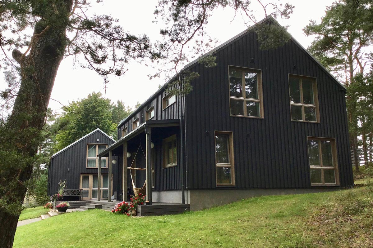 Ģimenes dzīvojamā māja pie jūras ar melnu koka apdares fasādi