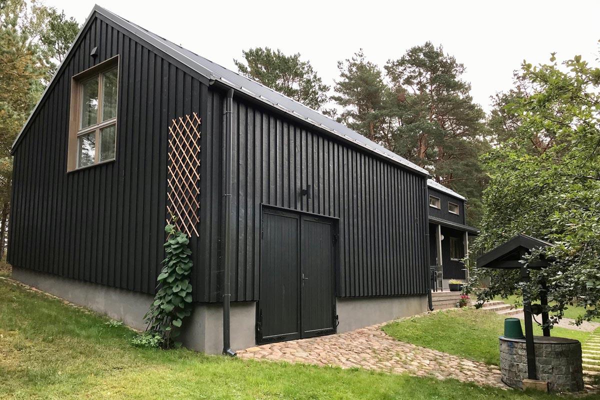 Melna koka saimniecības ēka ar zaļu zālu un aku