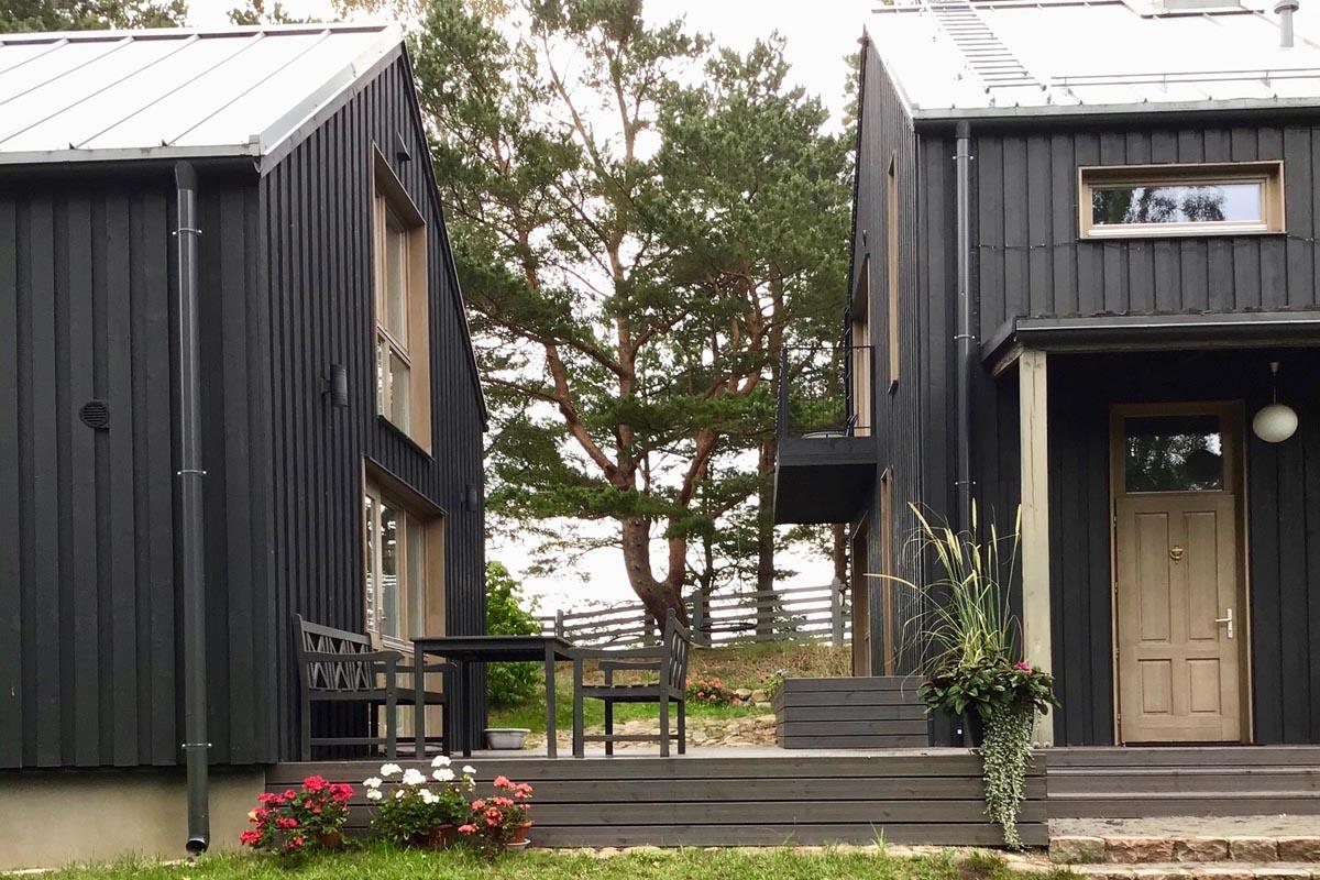 Pelēku koka dēļu terase starp divām melnām koka dēļu mājām ar skatu uz jūras kāpu ar priedi