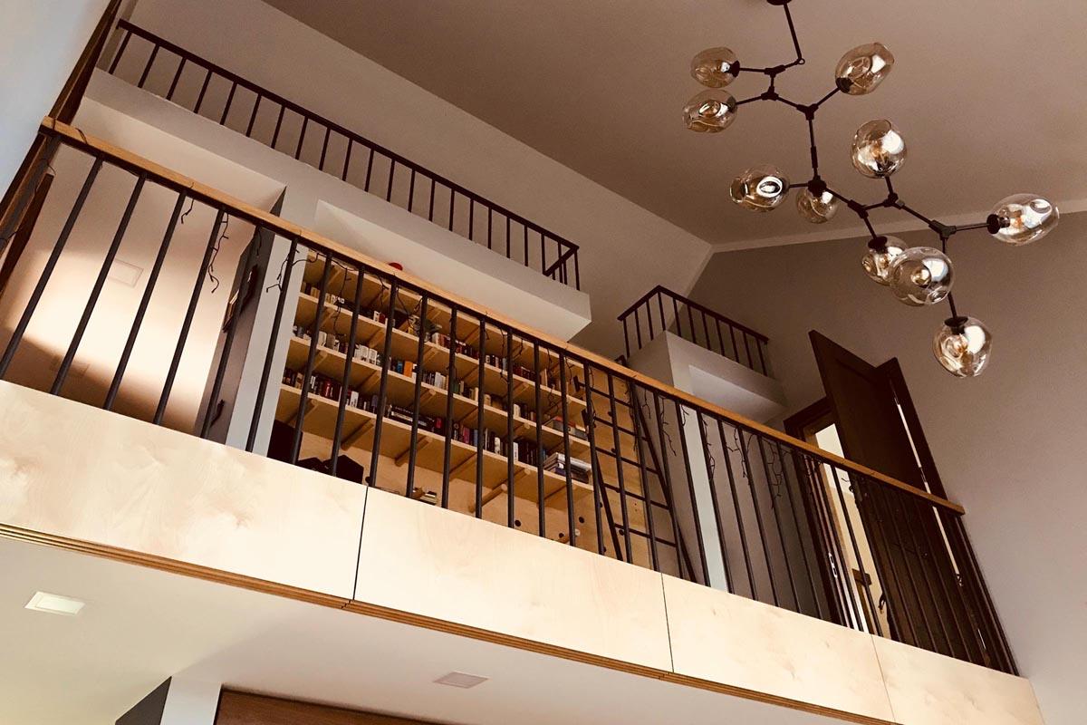 Mājas interjera dizains ar balkonu grāmatu plauktu un ķekaru lampu
