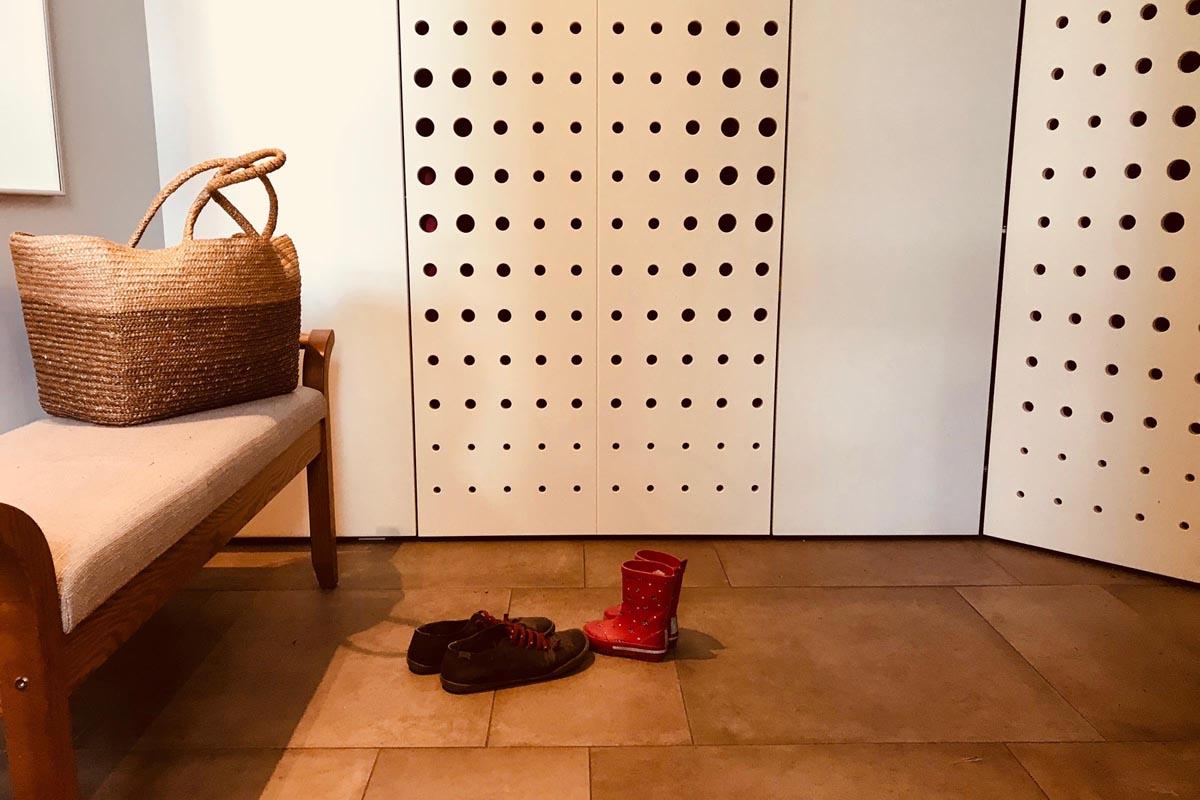 Interjera dizains ieejas hallei kur nolikt zābakus un kurpes apsēsties uz sola un skapja durvis ar puntveida caurimiem
