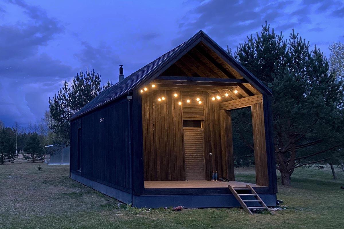 Nelielas tumša koka brīvdienu mājas arhitektūras fotogrāfija ar terasi priekšā vakara krēslā ar lampiņu virteni