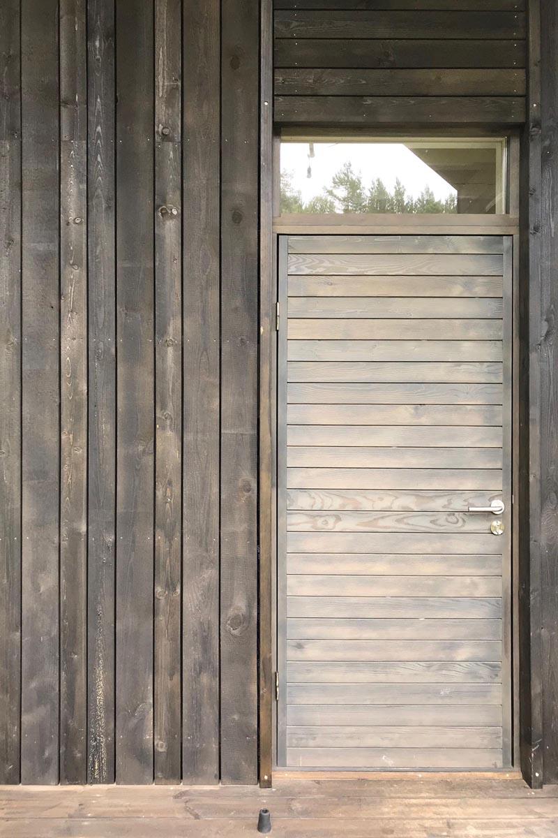 Pelēka horizontāla koka dēļu mājas ieejas durvis ar logu virs tām uz vertikālu dēļu fasādes fona
