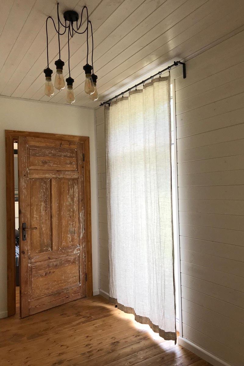 Interjera dizains ar atjaunotām koka durvīm griestos iekārtu lampu un lina aizkariem