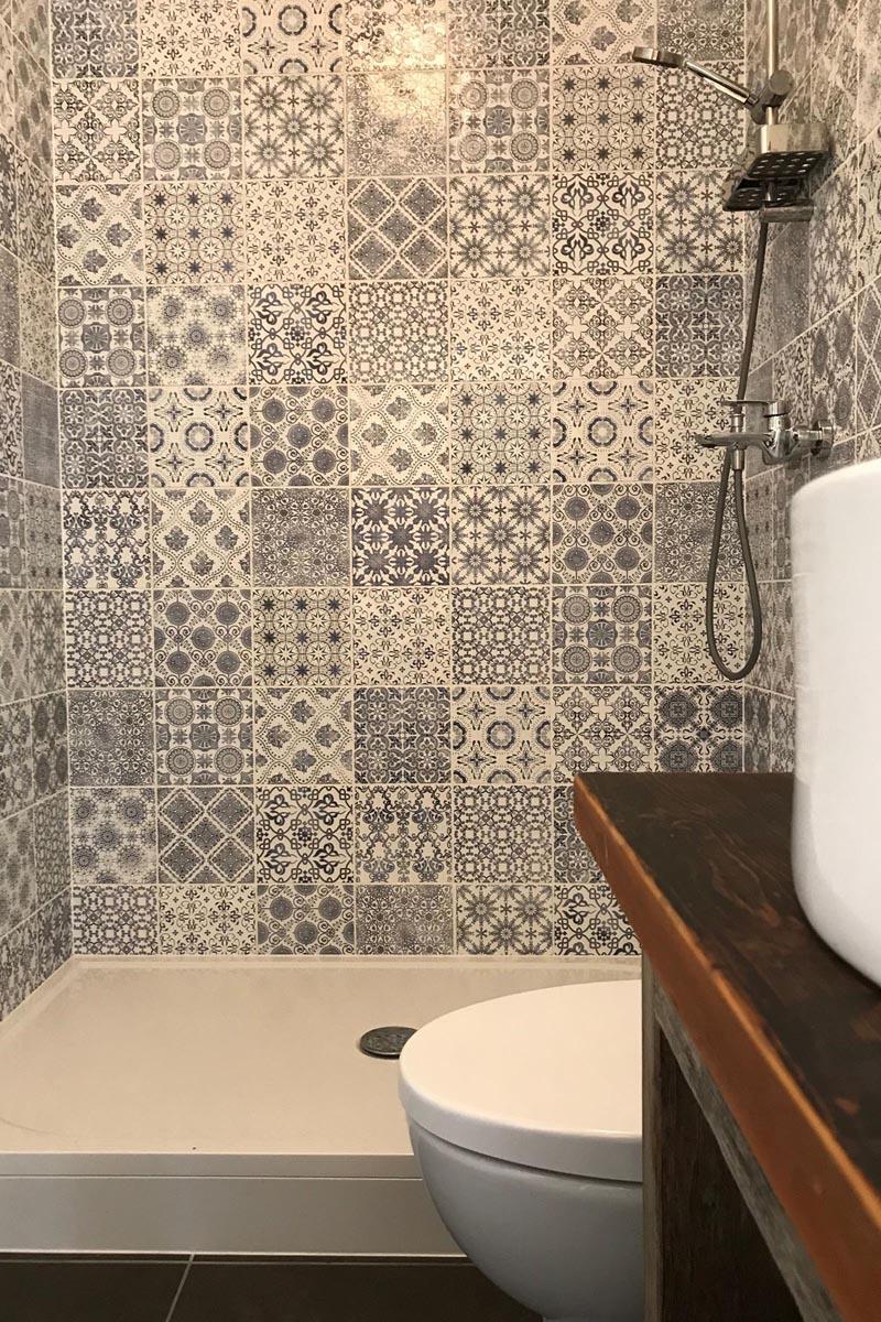Pelēkas rakstainas sienas flīzes pie dušas vannasistabā aiz koka izlietnes virsmas