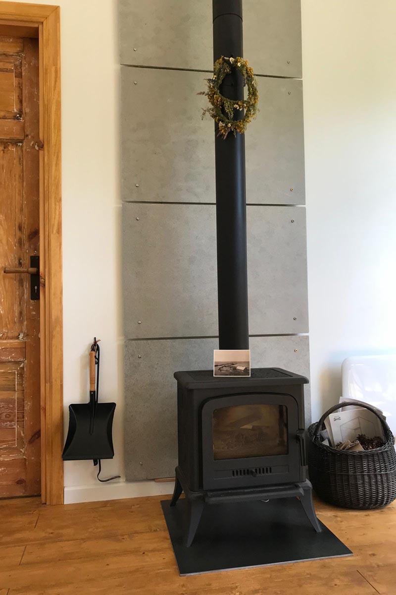 Melns kamīns ar skursteni ar uzkārtu vainagu malkas grozu uz grīdas un atjaunotām koka durvīm fonā