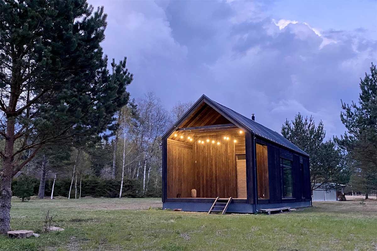 Brīvdienu māja projekts Pāvilosta ar melnu koka dēļu apdari un lampiņām fonā spilgti zilas mākoņainas debesis