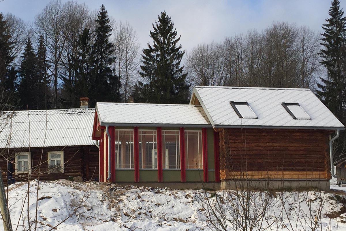 Guļbūves lauku sēta ar restaurētu klēts projektu un verandu sarkanos un zaļos toņos ziemā ar apsnigušu jumtu