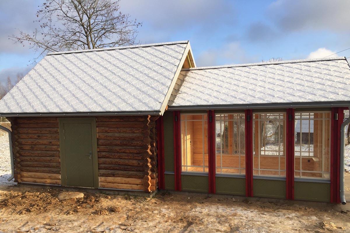 Guļbaļķu klēts restaurācijas projekts un veranda sarkanos un zaļos toņos ar koka pildiņiem un pelēku apsinigušu plākņu jumtu
