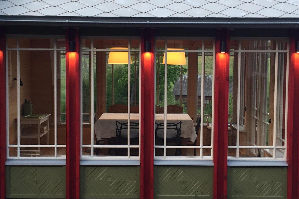 Veranda ar baltiem klasiski dalītiem logiem zaļiem koka pildiņiem fasādes apdarē un sarkanām vertikāli izgaismotām kolonnām